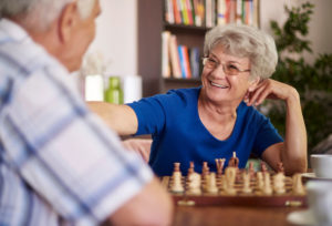 An older man plays chess with his wife and she appears to be winning